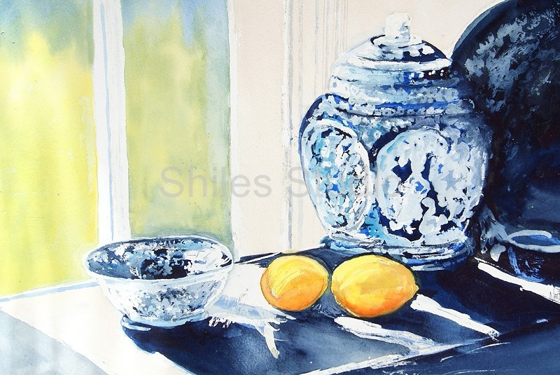 A blue ginger jar sits  in front of a window on a table with a bowl and two lemons