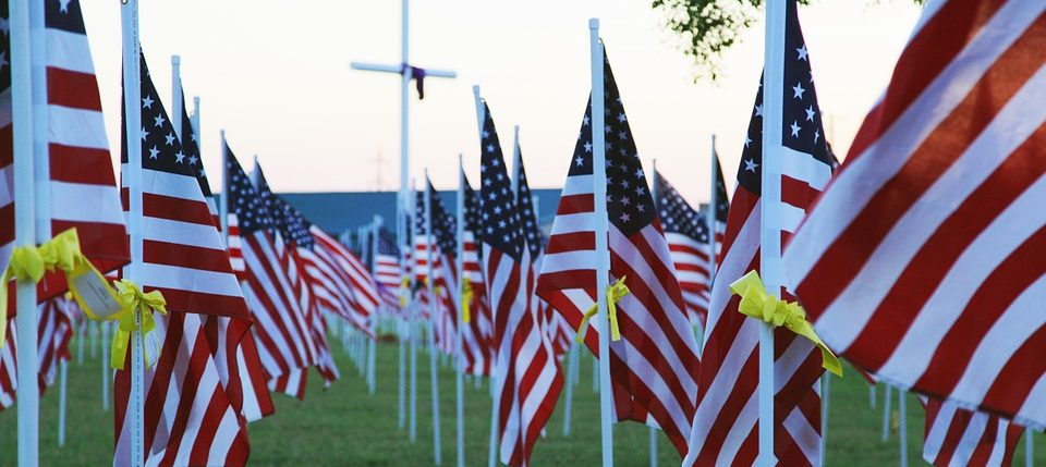 Line of flags with yellow ribbons tied to each flagpole and a cross in the background